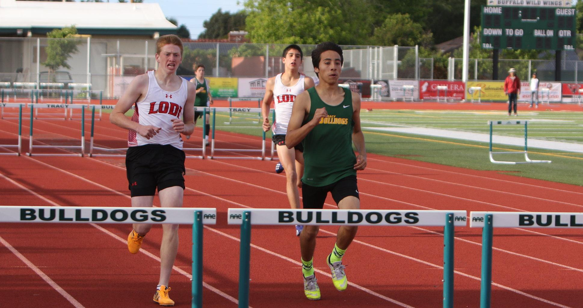 Kevin Hernandez races the 100-meter hurdles.