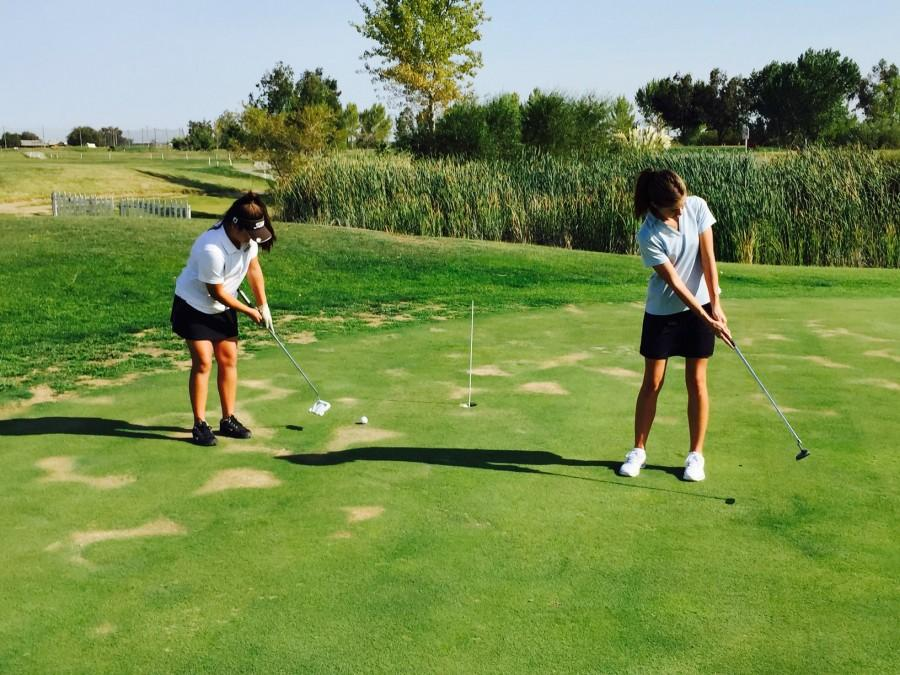 Players Kylee Takata and Lauren Goulart practice putting during practice.