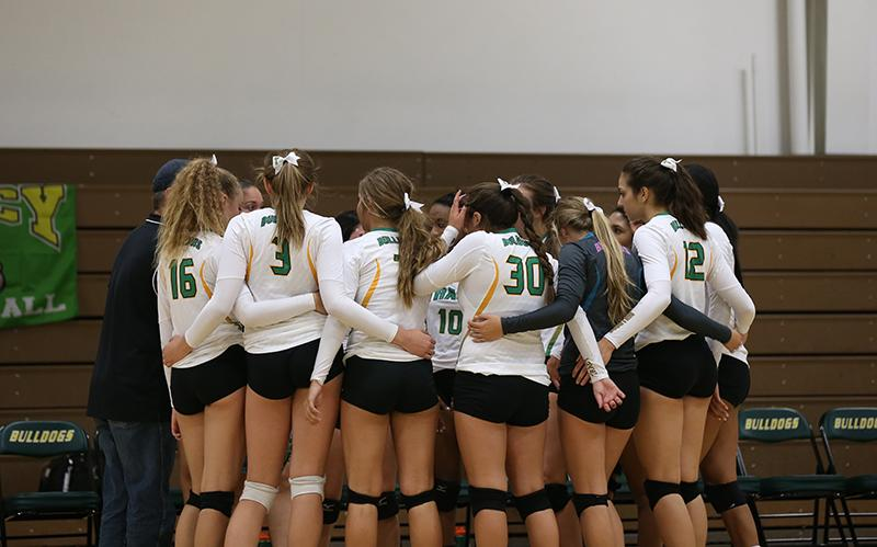 Varsity players huddle together before the game