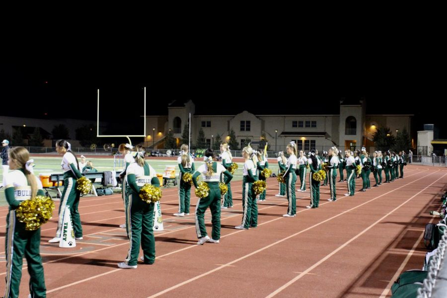 Varsity cheer and dance wait on the sidelines for Tracy to score another touchdown